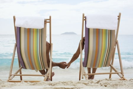 Couple on lounge chairs, holding hands (rear view), St. John, US Virgin Islands, USA photo