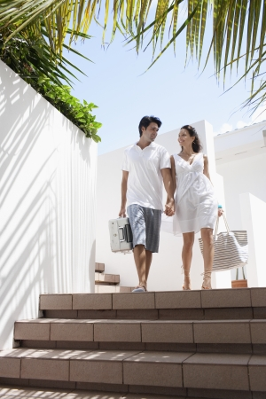 Young couple walking down steps with luggage photo