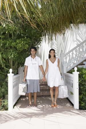 Young couple with luggage standing at resort photo