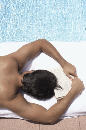 Young man sunbathing by pool (high angle view) photo