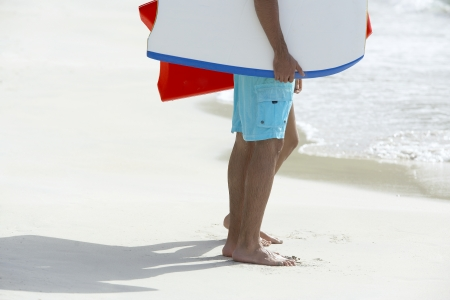 low section: Two people with bodyboards standing on beach (low section)
