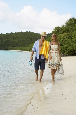 Mid adult couple walking on sandy beach, St. John, US Virgin Islands, USA photo