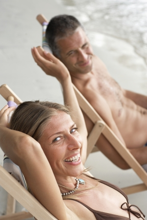 Mid adult couple on lounge chairs on beach photo
