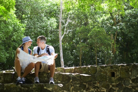 Mid adult couple reading map on ruins photo