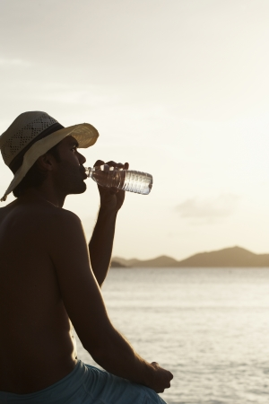 Young man drinking water on beach photo