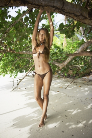 Mid adult woman in bikini stretching by trees, St. John, US Virgin Islands, USA photo