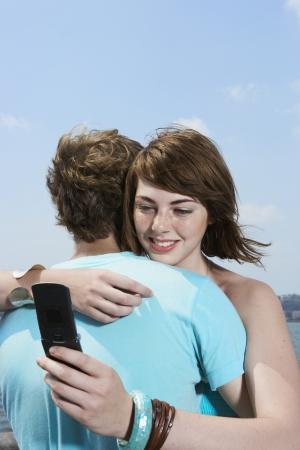 Teenage girl hugging boyfriend and using mobile phone photo