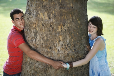 tree linked: Teenage couple hugging tree Stock Photo