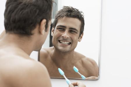 Mid adult man cleaning teeth photo