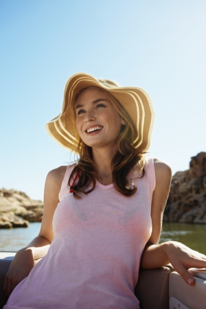 Young woman wearing sun hat on motorboat