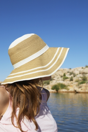 sun hat: Young woman in sun hat looking at lake Stock Photo