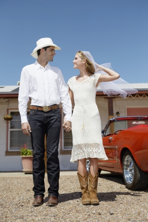 Portrait of newlyweds in cowboy attire at motel (low angle view) photo
