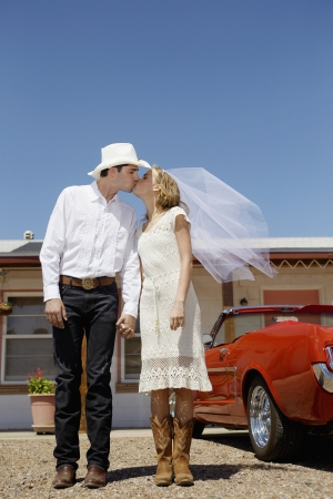 Newlyweds in cowboy attire kissing photo