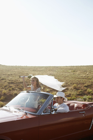 Newlyweds driving convertible through desert, Arizona, USA photo