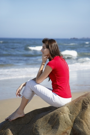 capri pants: Young woman sitting on rock and looking at ocean
