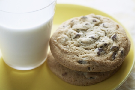 Chocolate chip cookies beside glass of milk (close-up) photo