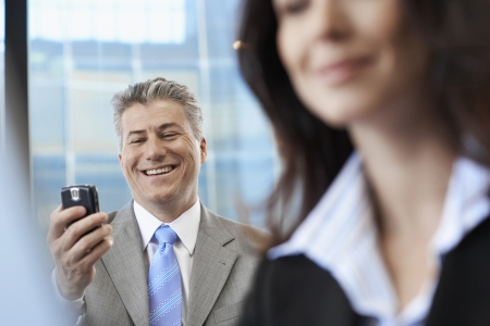 Businessman checking mobile phone near colleague photo