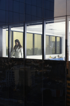 Businesswoman looking through office window (exterior view) photo