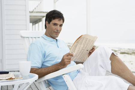 Mid adult man reading newspaper on lounge chair photo