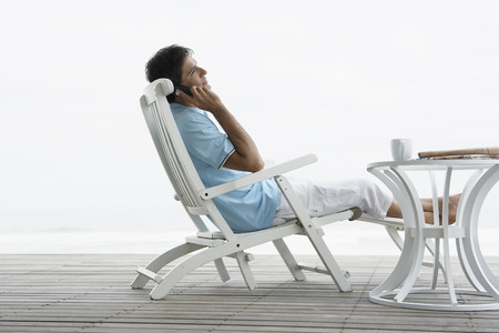 Mid adult man on phone near beach photo