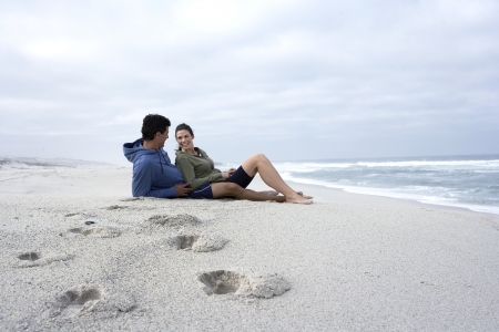 Mid adult couple sitting on sandy beach, Cape Town, South Africa photo