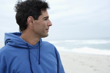 casual hooded top: Hombre de mediana edad que busca a ver en la playa