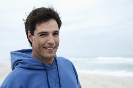 casual hooded top: Retrato de hombre de mediana edad en la playa