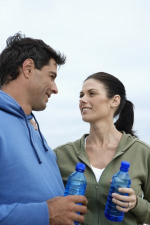 casual hooded top: Mediados de pareja de adultos con botellas de agua