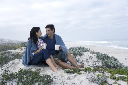 Mid adult couple drinking tea on beach, Cape Town, South Africa photo