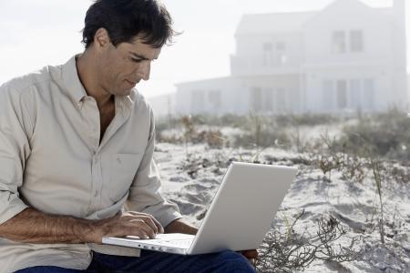 Mature man using laptop at beach photo