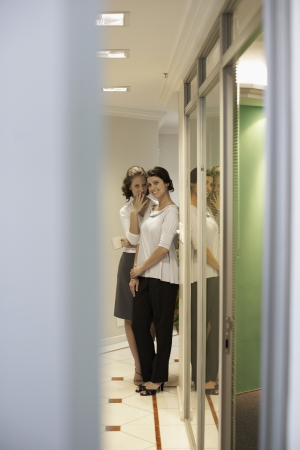 office politics: Two female office workers gossiping in corridor