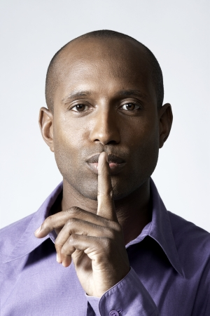 Mid adult man holding index finger on lips photo