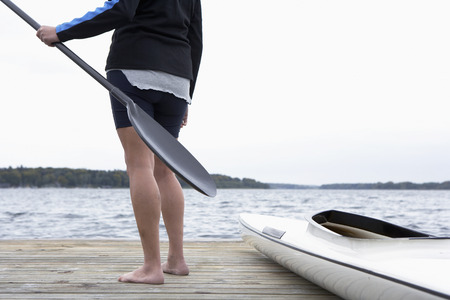 low section: Senior man holding oar by kayak (low section) Stock Photo