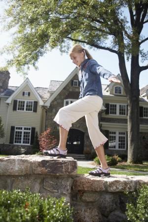 Girl walking on stone wall, Chatham, New Jersey, USA photo