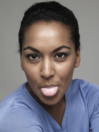 Young woman sticking out tongue photo