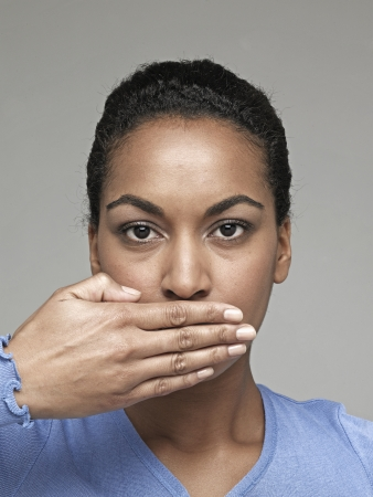 Young woman with hand over mouth photo