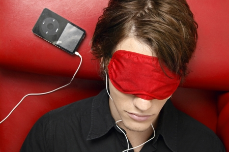 sleep mask: Young Man Wearing Sleep Mask and Listening to MP3 Player Stock Photo