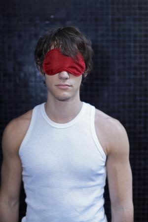 sleep mask: Young Man Wearing Sleep Mask Stock Photo