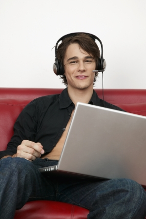 Young Man Listening to Music Through Laptop photo