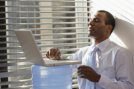 Mid Adult Man Using Laptop on Water Cooler photo
