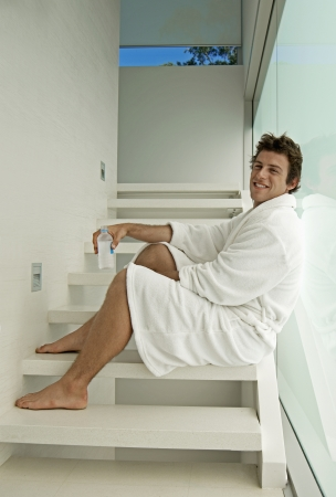 dressing gown: Young Man in Dressing Gown Drinking Water on Steps
