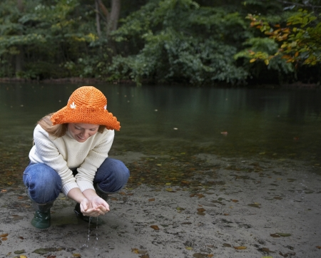 Woman Examining Water in Pond photo