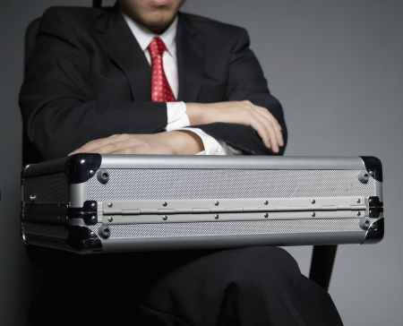 Businessman with Briefcase Sitting on Chair photo