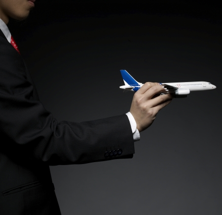 Businessman Holding Airplane Model photo