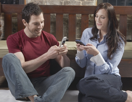 Couple Text Messaging on Floor photo