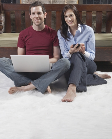 Couple Using Laptop and Mobile Phone photo