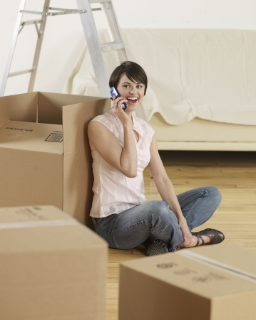 Young Woman on Cell Phone by Cardboard Boxes photo