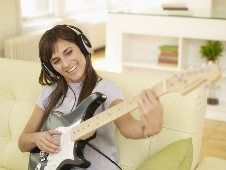 Mid-Adult Woman Playing Electric Guitar photo