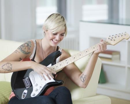 leis: Giovane donna che gioca chitarra elettrica