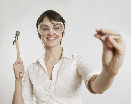 Young Woman with Goggles Holding Hammer and Nail photo